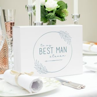 Landscape, face on view of the large white magnetic close gift box. Printed on the lid is a modern font that says to my best man steven with an arrow underneath. The text is surrounded by a circle that is accentuated with simplistic leaves in black