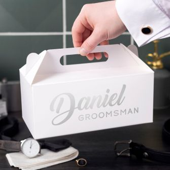Square white box with the words daniel groomsman printed on the front. Box is held by a male hand in shirtsleeves in front of black tiles. Watch, tie, cufflinks and belt are on the table in front.