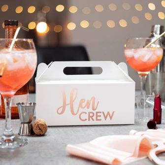 Large white party box with Hen Crew in metallic rose gold on the side. The box is pictured amongst cocktails and hen party accessories