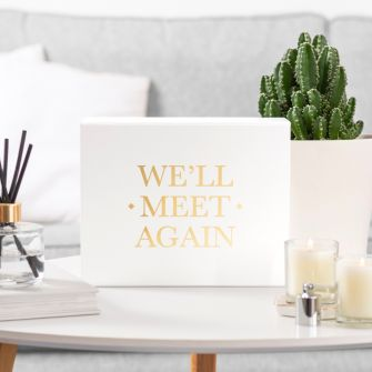 White magnetic gift box with metallic gold vinyl which says 'we'll meet again' in a living room setting